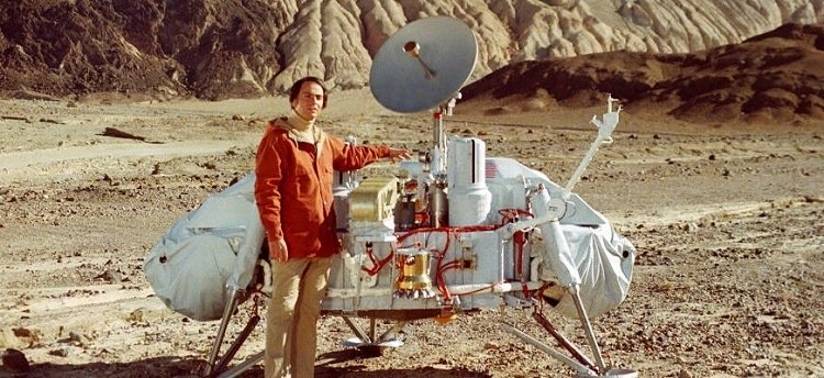 A photograph of Carl Sagan with a model of the Viking lander.