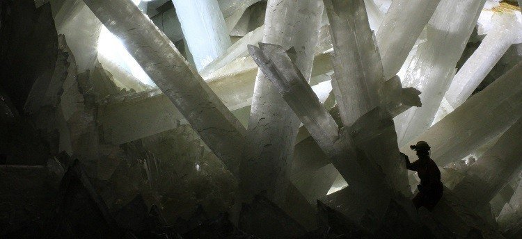 Photograph of a person surrounded by giant crystals.