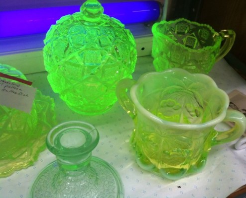 Photograph showing uranium glass glowing green under ultraviolet light.